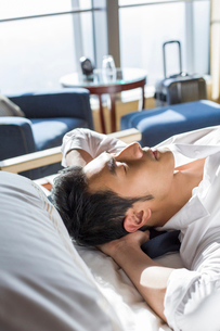 Young businessman resting in hotel roomの写真素材 [FYI02215475]