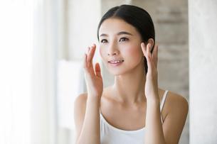 Young woman applying moisturizerの写真素材 [FYI02215479]