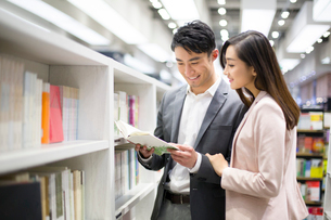 Young couple choosing books in bookstoreの写真素材 [FYI02215484]