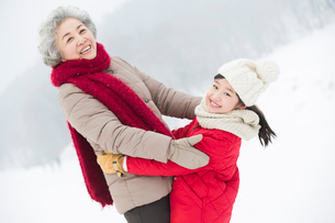 Happy grandmother and granddaughter embracing on the snowの写真素材 [FYI02215504]