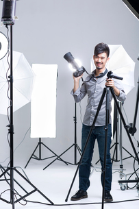 Photographer standing in studio with cameraの写真素材 [FYI02215548]
