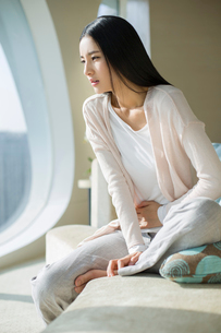 Young woman holding painful abdomen on sofaの写真素材 [FYI02215582]
