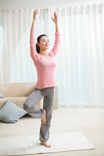 Young woman practicing yoga in living roomの写真素材 [FYI02215591]