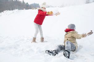 Two children having snowball fightの写真素材 [FYI02215597]