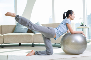 Young woman practicing yoga with fitness ballの写真素材 [FYI02215649]