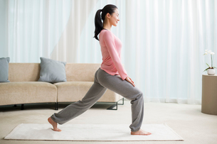 Young woman practicing yoga in living roomの写真素材 [FYI02215659]