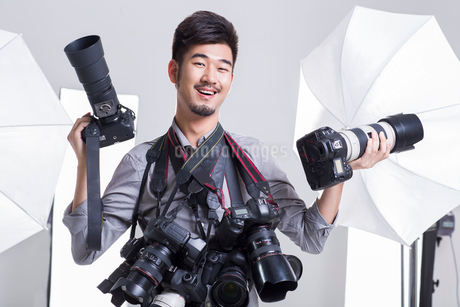 Portrait of photographer with many cameras hanging on his neckの写真素材 [FYI02215721]