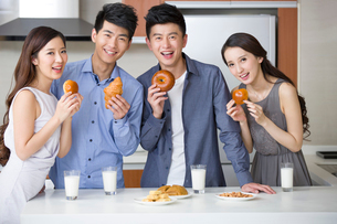 Happy young friends eating breakfast in the kitchenの写真素材 [FYI02215809]