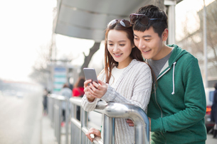 Young couple using smart phone at bus stopの写真素材 [FYI02215857]