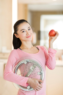 Happy young woman holding weight scale and appleの写真素材 [FYI02215878]