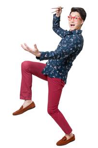Happy young man using chopsticksの写真素材 [FYI02215896]