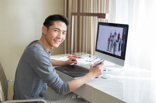 Young male fashion designer working at homeの写真素材 [FYI02215926]
