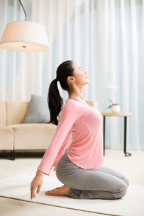 Young woman practicing yoga in living roomの写真素材 [FYI02215928]