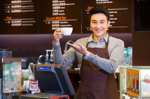Male coffee store clerk with cup of coffee in handの写真素材 [FYI02215932]