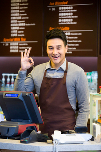 Male coffee store clerk doing OK signの写真素材 [FYI02215937]