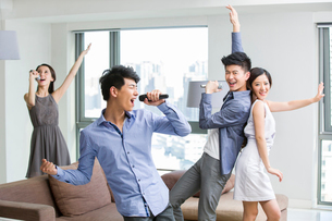 Happy young friends singing and dancing in living roomの写真素材 [FYI02215951]