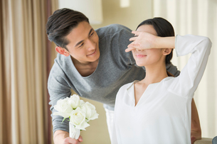 Young man surprising wife with flowersの写真素材 [FYI02215988]