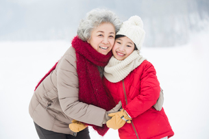 Happy grandmother and granddaughter embracing on the snowの写真素材 [FYI02216012]