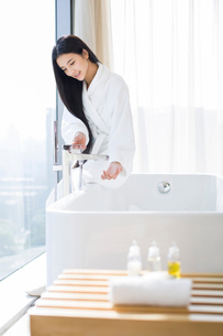 Young woman filling bathtubの写真素材 [FYI02216056]