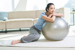 Happy young woman leaning on fitness ballの写真素材 [FYI02216087]