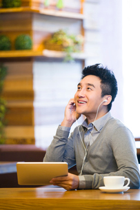 Young man enjoying music in digital tablet in coffee shopの写真素材 [FYI02216093]