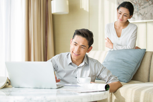 Young man working at home while his wife looking at himの写真素材 [FYI02216143]