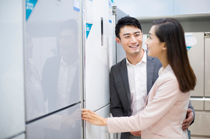 Young couple buying refrigerator in electronics storeの写真素材 [FYI02216264]