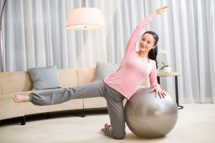 Young woman practicing yoga with fitness ballの写真素材 [FYI02216333]