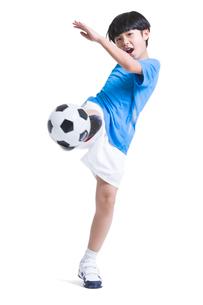 Cheerful boy kicking footballの写真素材 [FYI02216362]