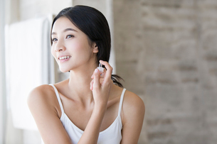 Young woman spraying perfume on her neckの写真素材 [FYI02216396]