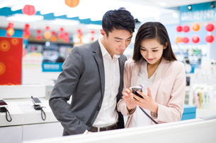 Young couple looking at smart phone in electronics storeの写真素材 [FYI02216415]