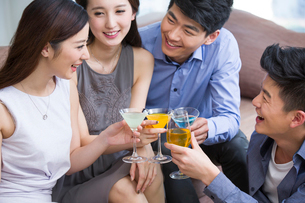 Happy young friends drinking cocktail in living roomの写真素材 [FYI02216420]