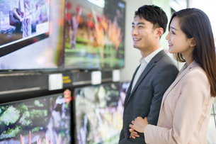 Young couple buying television in electronics storeの写真素材 [FYI02216440]