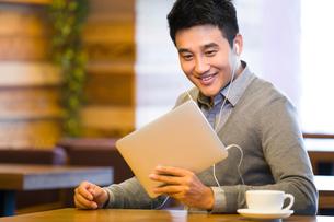 Young man enjoying videos in digital tablet in coffee shopの写真素材 [FYI02216450]