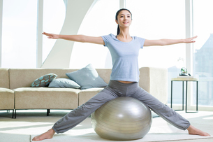 Young woman practicing yoga with fitness ballの写真素材 [FYI02216461]