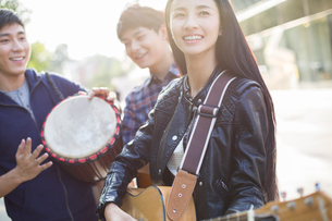 Young adults playing musical equipment on streetの写真素材 [FYI02216549]