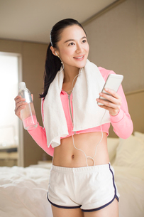 Young woman listening to music after exerciseの写真素材 [FYI02216576]