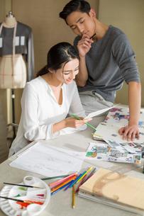 Two fashion designers drawing sketchの写真素材 [FYI02216597]