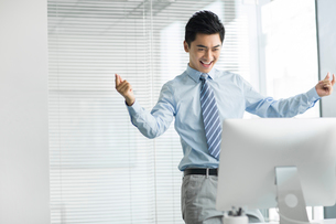 Cheerful young businessman using computer in officeの写真素材 [FYI02216628]