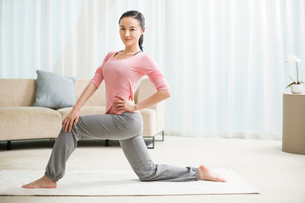 Young woman practicing yoga in living roomの写真素材 [FYI02216632]
