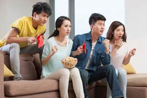 Young adults watching sports games on TVの写真素材 [FYI02216674]