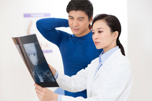 Doctor looking at x-ray image with patientの写真素材 [FYI02216681]