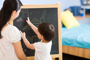 Mother and daughter drawing on blackboardの写真素材 [FYI02216693]