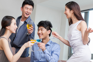 Happy young friends drinking cocktail in living roomの写真素材 [FYI02216707]