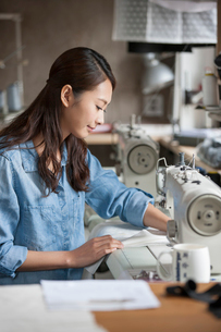 Fashion designer working with sewing machine in studioの写真素材 [FYI02216709]