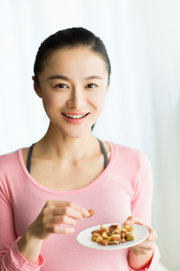 Happy young woman eating nutsの写真素材 [FYI02216920]