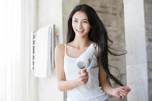 Young woman drying her hair with a hair dryerの写真素材 [FYI02216933]