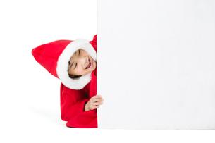 Little girl hiding behind a blank whiteboardの写真素材 [FYI02216948]