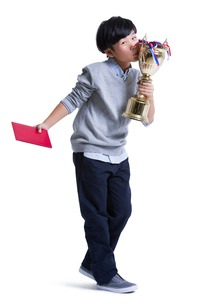 Cheerful boy with certificate and trophyの写真素材 [FYI02216994]