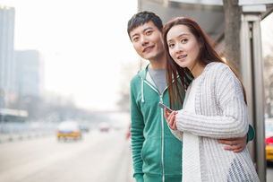 Young couple waiting at bus stopの写真素材 [FYI02217028]